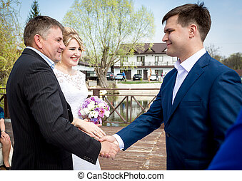 brides father shaking hands with groom at wedding ceremony -...