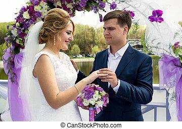 handsome smiling groom putting ring on brides hand -...
