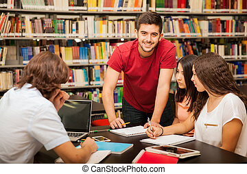 Studying together at school - Handsome Latin man helping his...