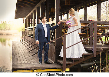 bride and handsome groom walking down the stairs on pier -...