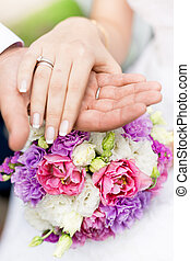 soft focus photo of groom holding brides hand on bridal bouquet