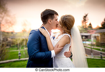 elegant newly married couple kissing in park at sunset