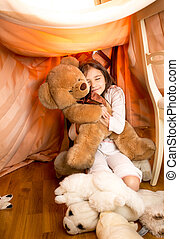 little girl playing with teddy bear in self-made house -...