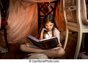 cute girl sitting under blanket and reading a book -...