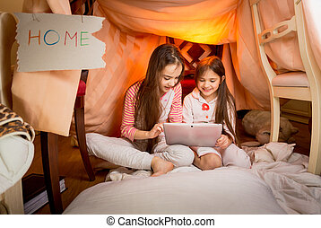 girls sitting in house made of blankets and using digital...
