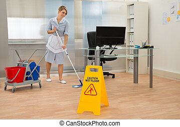 Maid Cleaning Floor In Office - Young Maid Cleaning Floor...