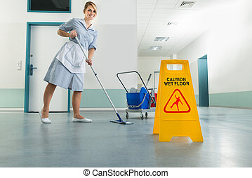 Janitor With Mop And Wet Floor Sign - Happy Female Janitor...