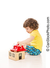Toddler boy playing with wooden house against white...