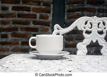 cup of coffee on vintage wrought iron garden table