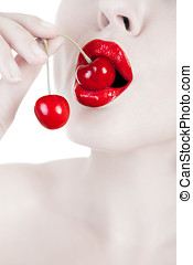 Mouth with red lips biting cherry