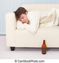Person comfortable sleeps on sofa having got drunk beer -...