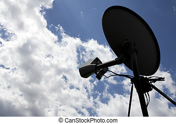 Silhouette of a satellite dish with clouds in the background