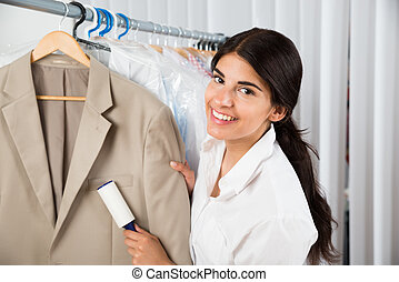 Cleaner In Laundry Shop With Adhesive Roller - Female...