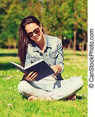 smiling young girl with book sitting in park - lifestyle,...