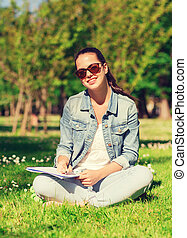 smiling young girl with notebook writing in park -...
