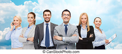 group of smiling businessmen over blue sky - business,...