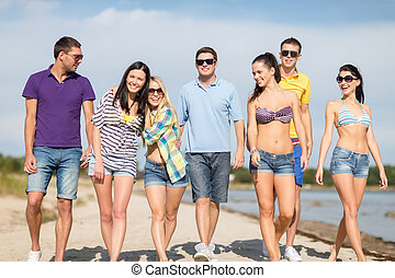group of happy friends walking along beach - summer...