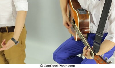 Vigorous concert of the musical group consists of guitarist, singer and DJ in the studio on a white background