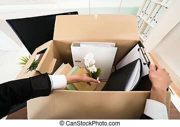 Businesswoman Packing Personal Belonging In Box - High Angle...