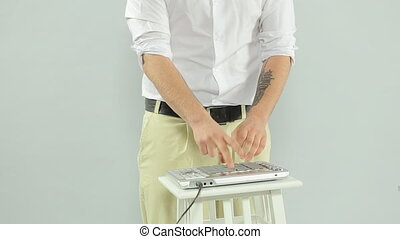 Talented guy playing on DJ midi controller in the studio on a white background