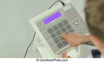 Close up of DJ mixing music on a panel of the midi...