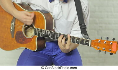 Talented enthusiastic guitarist playing the guitar sitting in the studio on a white background