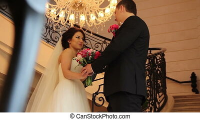 groom and bride handing the wedding bouquet on stairs