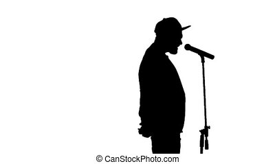 Black silhouette of guy in a cap singing a song and...
