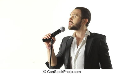 Brutal man with a beard sings into the microphone in a...