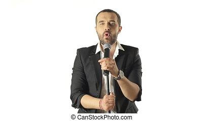 Attractive blue-eyed man in a jacket sings into the microphone in a studio on a white background