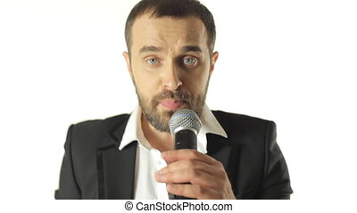 Close-up of a young handsome man energetically singing the song into the microphone in a studio on a white background