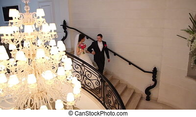 wedding couple going downstairs - bride and groom going...