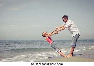 Father and daughter playing on the beach at the day time.