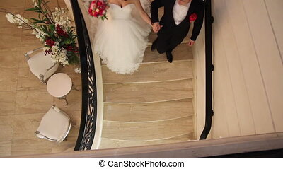 wedding couple handing and going downstairs