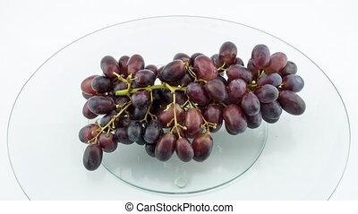 Grape disappears from glass table, stop motion.