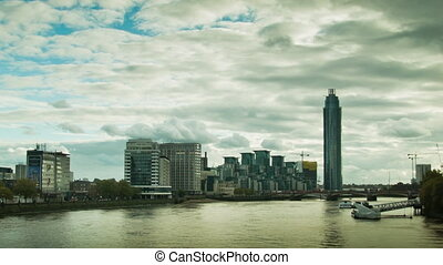 Riverside walk and the Thames, London. Cloudy sky with...