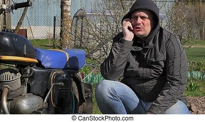 Man talking on cell phone near old motorcycle at outdoor