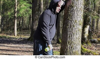 Tired runner with overweight drink from  bottle in the park