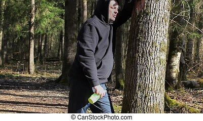 Tired runner with overweight near tree in the park
