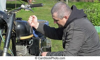 Man repairing old motorcycle at outdoor