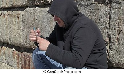 Drug addict man with syringe in hand near wall