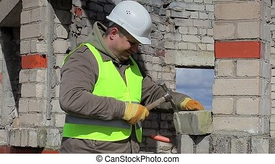 Construction worker with mallet and brick