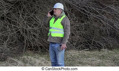 Forest engineer talking on cell phone near pile of twigs