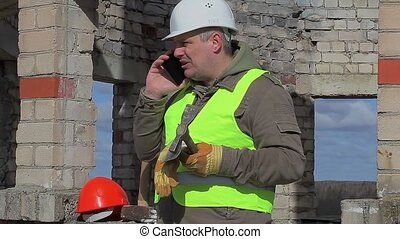 Angry construction worker with cell phone, trowel and mallet
