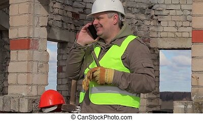 Construction worker with cell phone, trowel and mallet