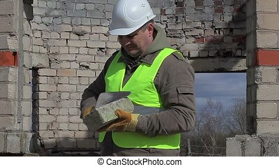 Construction worker with trowel and brick