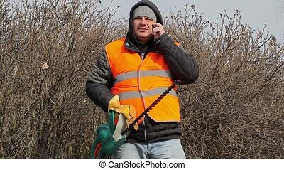 Landscape worker with bush cutter talking on cell phone