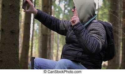Hiker with tablet PC made selfie in forest