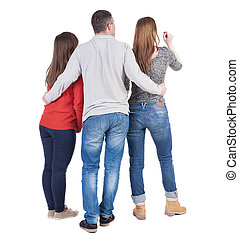 Back view of three friends (woman and man). A guy in a gray...