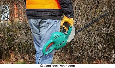 Landscape worker with bush cutter at outdoor